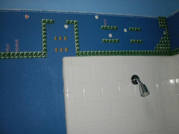 Banheiro geek tem paredes decoradas com o tema Super Mario Bros.