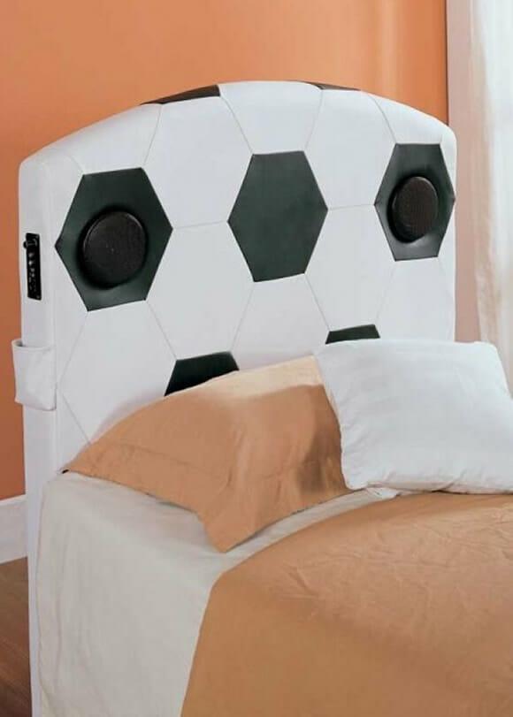 Uma cama com cabeceira que imita bola de futebol e com speakers embutidos.