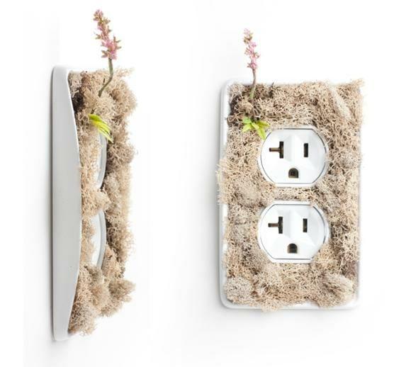 """Interruptores e tomadas cobertos por plantas incentivam usuários a """"pensar verde""""."""