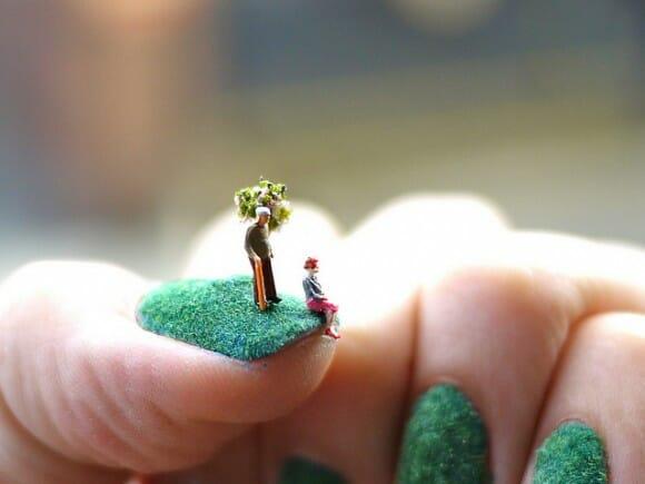 Arte nas mãos - Cenas em miniatura sobre um gramado nas unhas