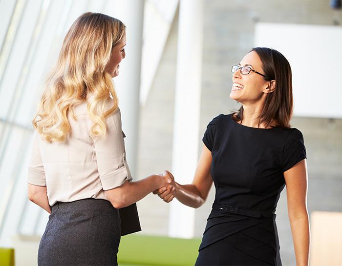 Two Businesswomen Shaking Hands In Modern Office
