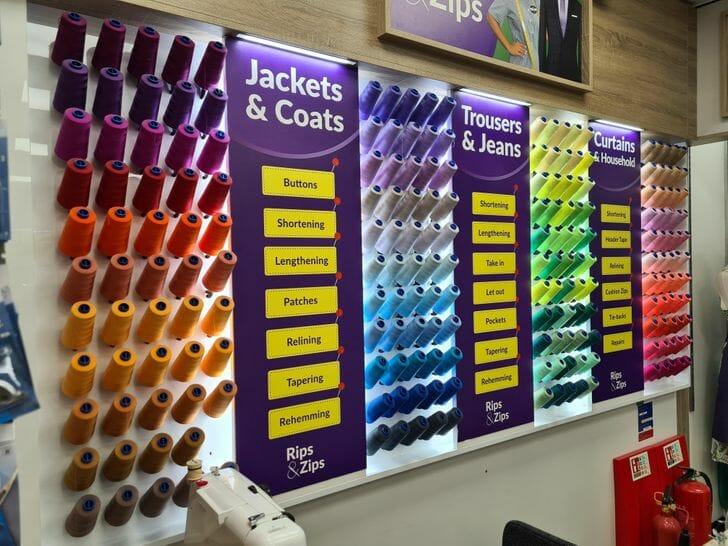 rolos de linhas organizadas por cores em uma loja de aviamentos